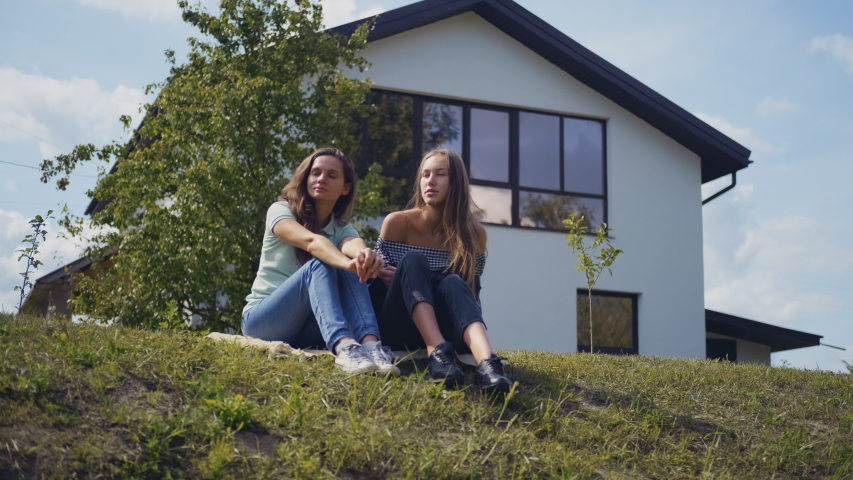 Two young women spend outdoors, sitting on grass and communicate on different topics.   Shutterstock HD Video #1038872591