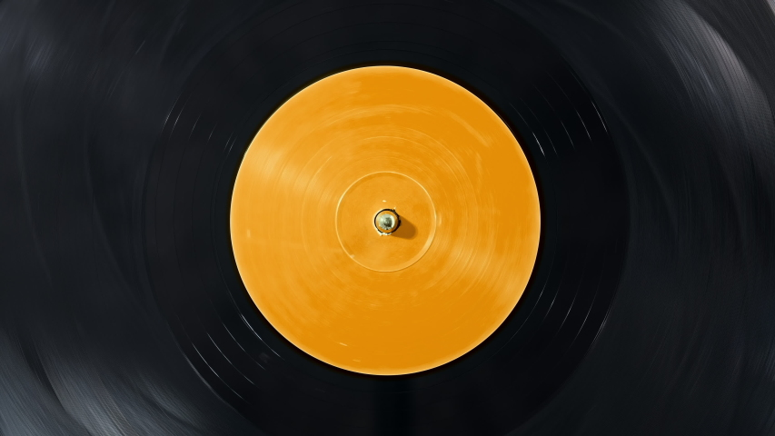 Black vinyl record on a DJ turntable. Black vinyl background with yellow screen in the center. Rotating plate close up. Party. Loop. Macro View from above. Popular Disco Trends 60s, 70s, 80s, 90s | Shutterstock HD Video #1038899021