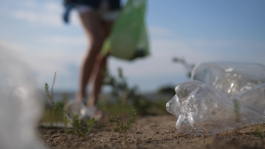 Plastic pollution of nature. Volunteer picking up trash on the beach.   Shutterstock HD Video #1038911201