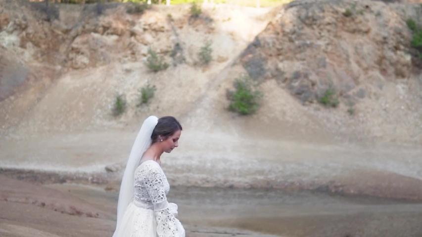 Beautiful Woman In A White Wedding Dress Near A Pond | Shutterstock HD Video #1038953081