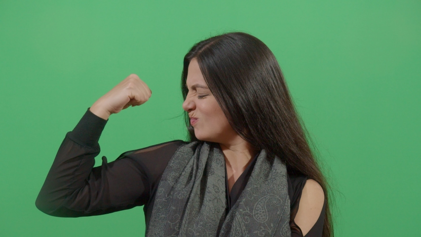 Woman Flexing Muscle Trying To Suggest Power. Studio Isolated Shot Against Green Screen Background | Shutterstock HD Video #1039150871