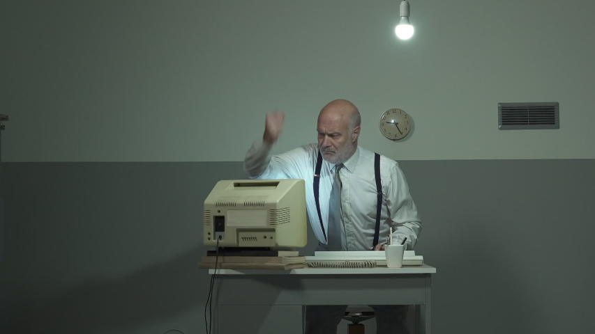 Angry mature businessman sitting at desk and hitting his outdated old computer | Shutterstock HD Video #1039230461