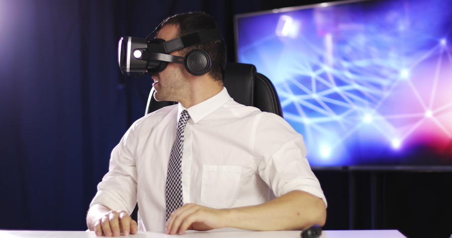 Young businessman uses virtual reality glasses indoors. The man turns the pages looking in 3D virtual reality headset. | Shutterstock HD Video #1039247471