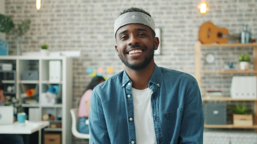 Portrait of joyful African American man in casual clothing smiling looking at camera in office indoors. Emotions, modern business and workplace concept. | Shutterstock HD Video #1039280591