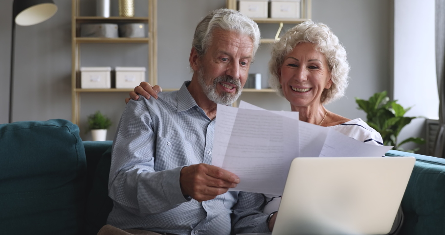 Happy old couple talking checking papers holding domestic bills and laptop computer, satisfied bank clients senior grandparents customers planning budget investment loan insurance payment at home | Shutterstock HD Video #1039338011