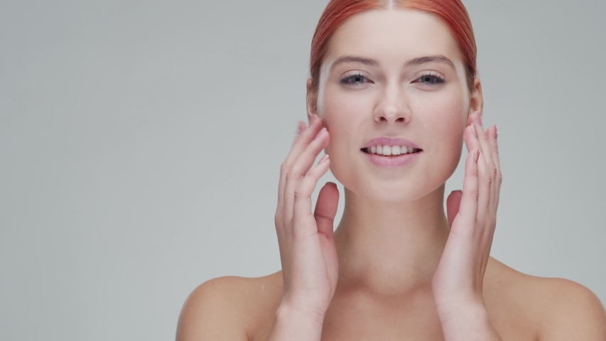 Studio portrait of young, beautiful and natural redhead woman applying skin care cream. Face lifting, cosmetics and make-up. | Shutterstock HD Video #1039342031