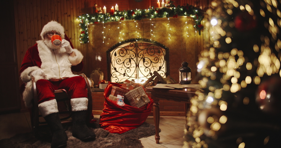 Authentic santa claus sitting in his rocker near christmas tree and srinking tea or cocoa - christmas spirit, holidays and celebrations concept 4k footage   Shutterstock HD Video #1039427501