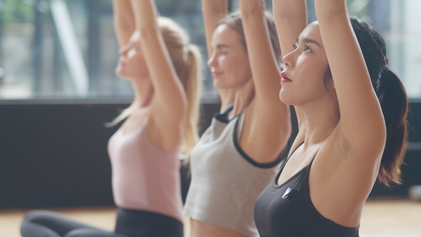 Young diversity sporty people practicing yoga lesson with instructor. Multi racial group of women exercising healthy lifestyle in fitness studio. Sport activity, gymnastics or ballet dancing class.   Shutterstock HD Video #1039751681