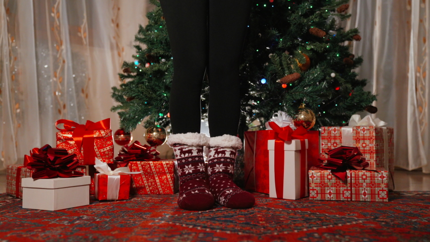 Close-up of slim woman's legs in knitted warm winter socks staying next to christmas tree decorations. Girl's legs and red christmas gift boxes under the tree. Flashing garland on the tree | Shutterstock HD Video #1039756061