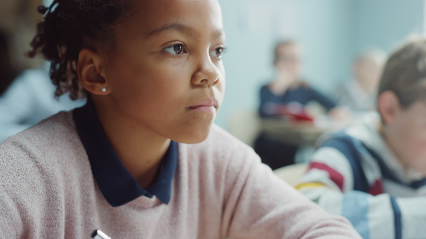 In Elementary School Classroom Brilliant Black Girl Writes in Exercise Notebook, Taking Test. Junior Classroom with Diverse Group of Bright Children Working Diligently and Learning. Portrait