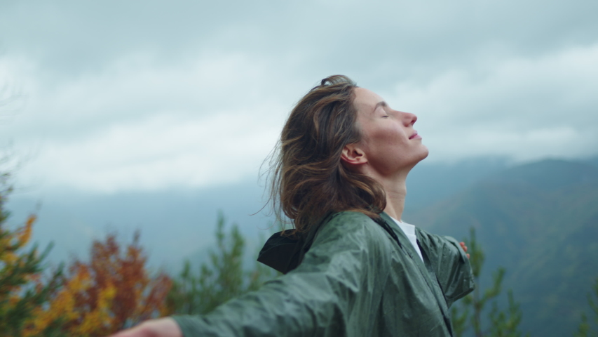 Free Happy Young Hiker Woman in green raincoat looking up with raised arms enjoying calm rainy day in the nature breathing fresh air, hair blowing in wind, People Mountains Freedom Concept, Happiness | Shutterstock HD Video #1039980731