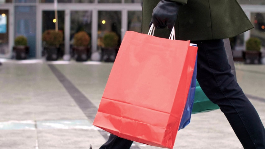Low section of man with shopping bags walking the street | Shutterstock HD Video #1040321321