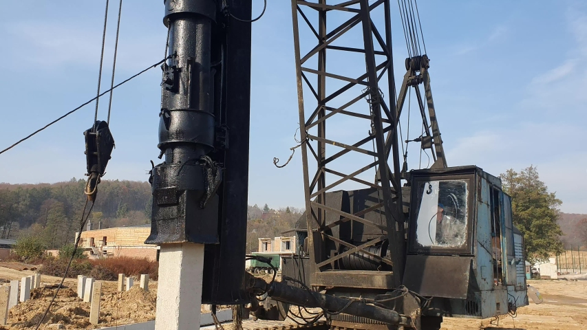 Machine drives into the ground piles construction. Construction of the Foundation of reinforced concrete structures. | Shutterstock HD Video #1040440691