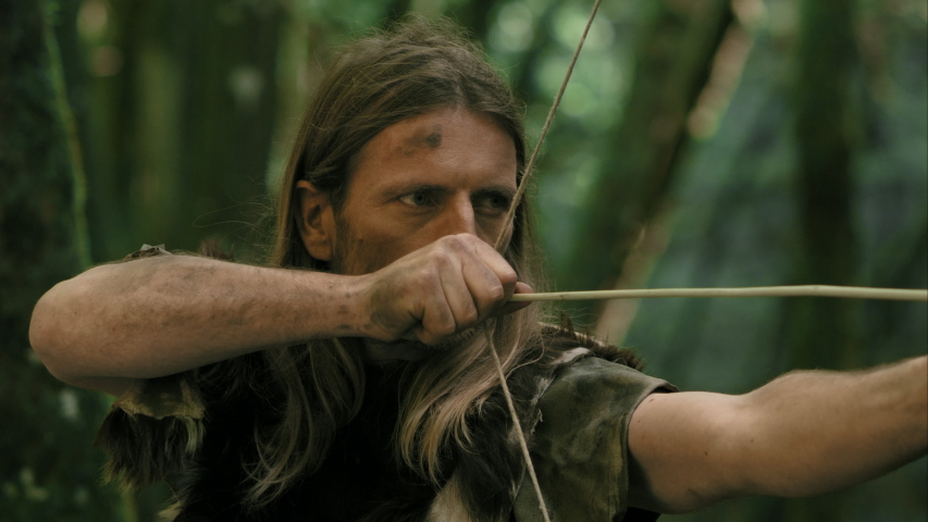 Prehistoric Man With Rudimentary Bow And Arrow Shoots And Hits Target | Shutterstock HD Video #1040461421