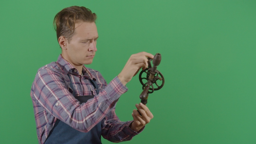Adult Man Carpenter Testing A Drill On The Green Screen. Studio Isolated Shot Against Green Screen Background | Shutterstock HD Video #1040502731