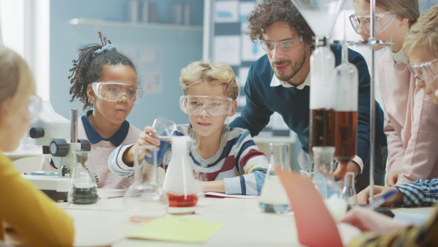Elementary School Science Classroom: Enthusiastic Teacher Explains Chemistry to Diverse Group of Children, Little Boy Mixes Chemicals in Beakers. Children Learn with Interest | Shutterstock HD Video #1040541401