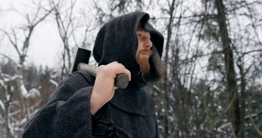 Tracking Shot Bearded Hooded Man Walking Through Woods With Hammer On Shoulder | Shutterstock HD Video #1040605301