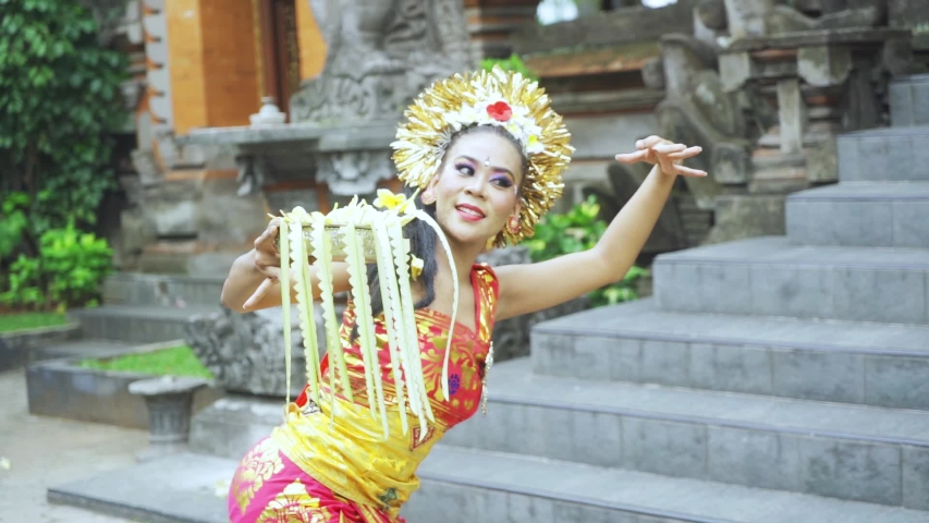 Slow motion of attractive balinese dancer holding a frangipani flower while dancing in the temple | Shutterstock HD Video #1040676521