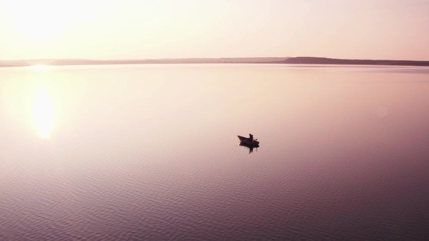 Silhouette of fishermen alone in a boat swimming on a big lake / sunset background - aerial drone view | Shutterstock HD Video #1040698481