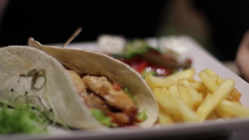 A pretty girl eats food in a restaurant   Shutterstock HD Video #1040733821