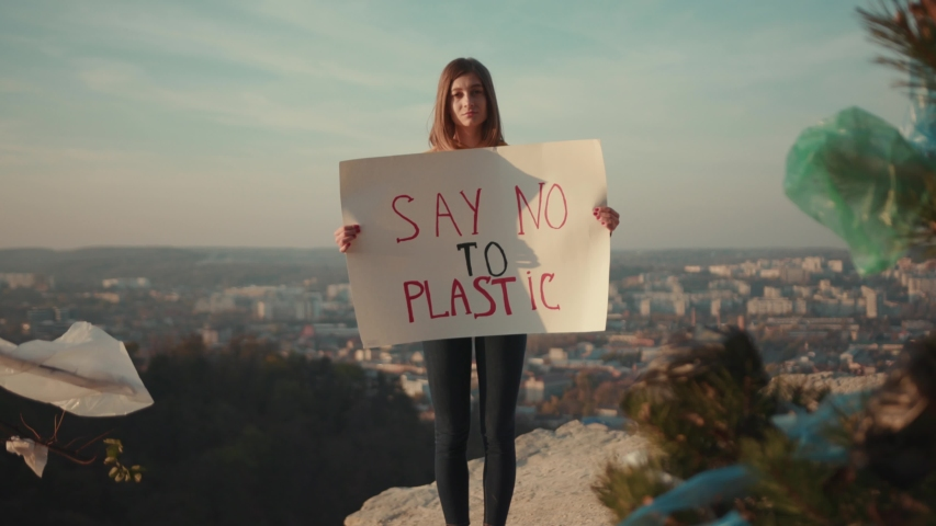 Sad woman activist holding encouraging white poster Say no to plastic standing background beautiful view nature environmental community earth eco environment outdoor recycle trash waste slow motion   Shutterstock HD Video #1040767601