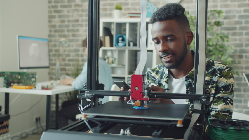 African American guy engineer is using 3d printer in office enjoying modern technology creating new model. People, occipation and innovation concept.