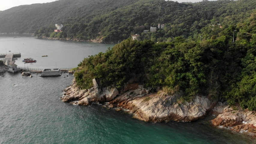 Aerial view a drone flew over a rock on which waves are breaking. We offer a view of the bay with villas. Lamma Island, Hong Kong   Shutterstock HD Video #1040818931