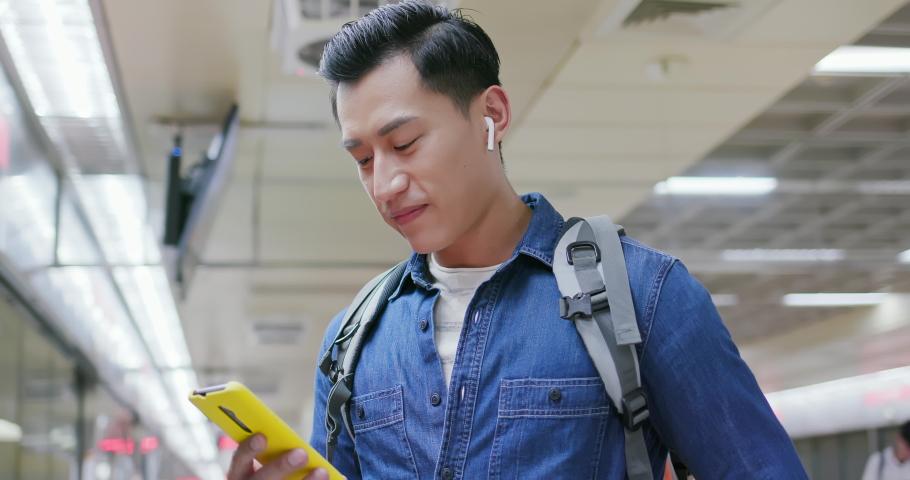Asian man use wireless earbuds to listen music on the mrt station | Shutterstock HD Video #1040827271