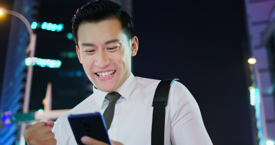 Businessman use the smart phone and feel excited while wander | Shutterstock HD Video #1040827661