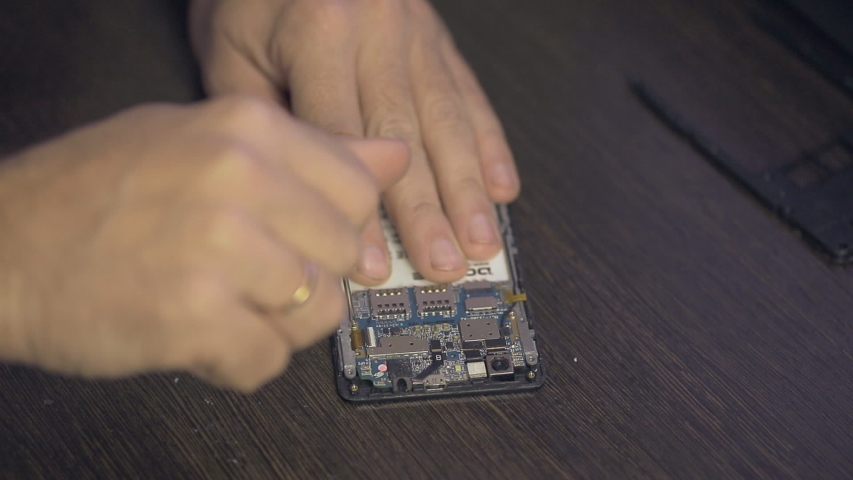 Cell phone repair, a man disassembles the body of the smartphone | Shutterstock HD Video #1040846231