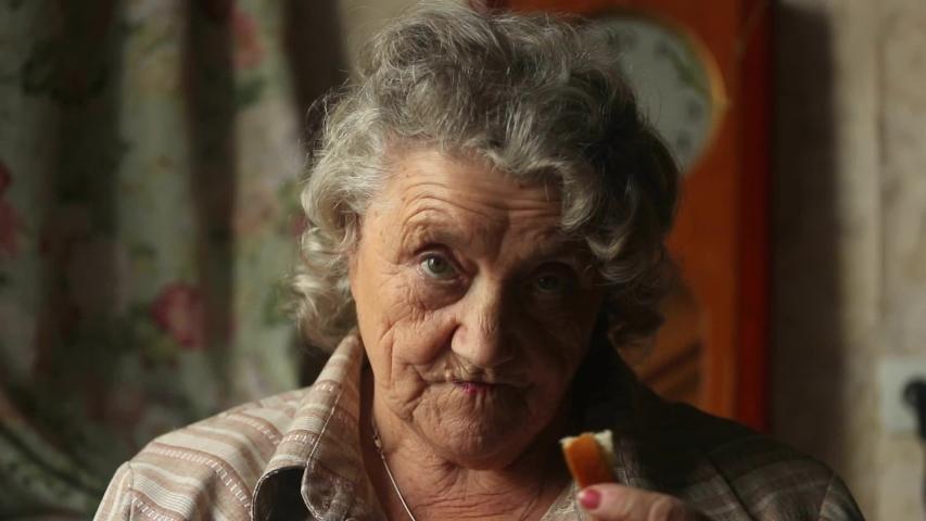 Smile elderly woman eating bread | Shutterstock HD Video #1040876891