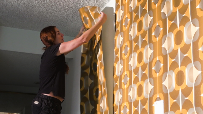 Real woman improving, renovating and decorating her home by hanging 1970's retro wallpaper | Shutterstock HD Video #1040883191