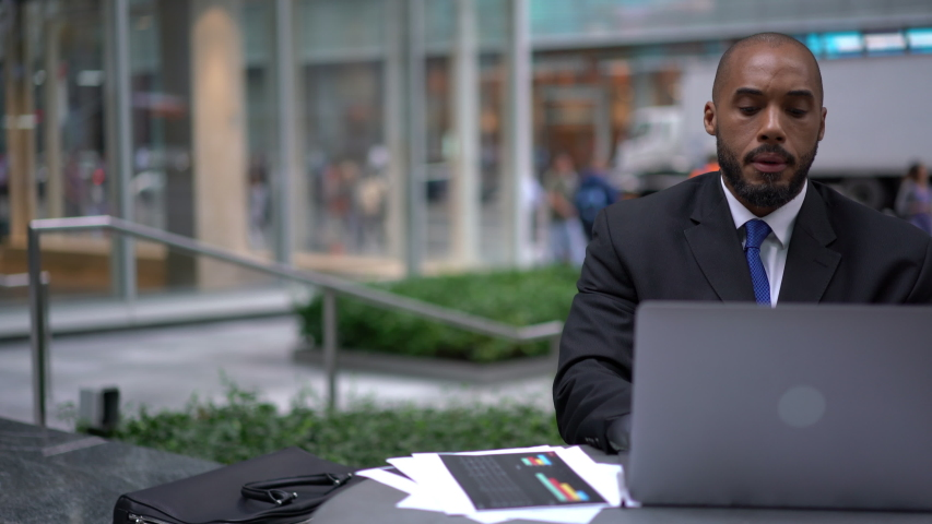 African American male entrepreneur in formal wear using public internet connection on modern laptop device for online accounting for documents sitting in cafe terrace, analyze of capital investment | Shutterstock HD Video #1040953841