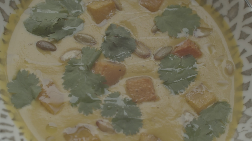 Pumpkin soup. Close up view. Yellow soup decorated with greens and pieces of baked pumpkin | Shutterstock HD Video #1040974691