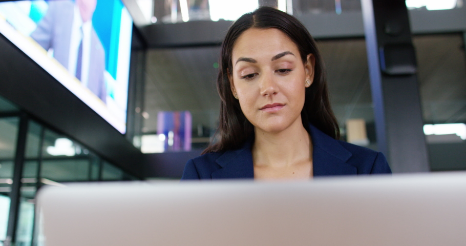 4K Businesswoman working on laptop with electronic screen displaying business & news reports | Shutterstock HD Video #1041089701