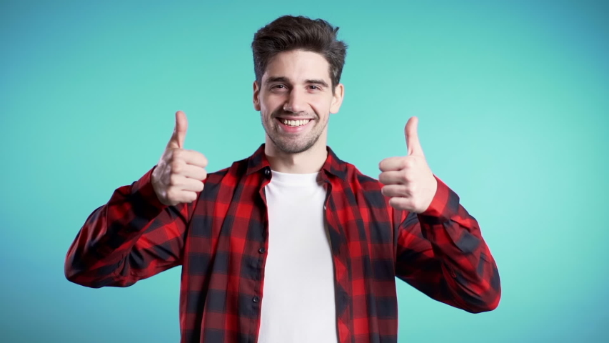 Positive young man smiles to camera. Hipster guy showing thumb up sign over blue background. Winner. Success. Body language. | Shutterstock HD Video #1041091171