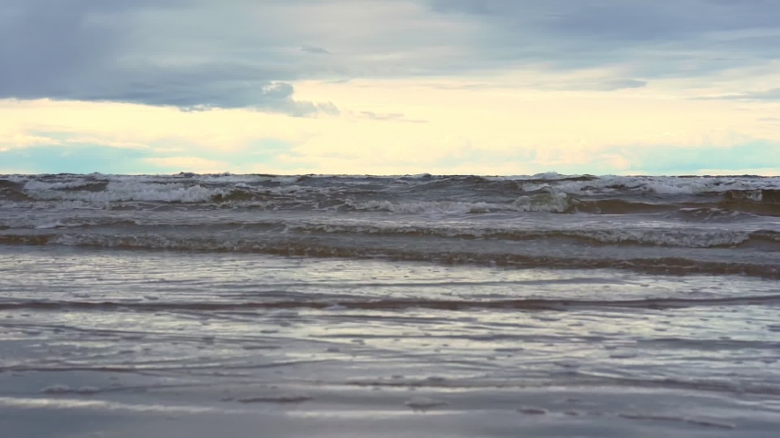 Large sea waves roll on sand beach surface creating white foam under grey cloudy sky with sunlight on horizon slow motion | Shutterstock HD Video #1041149161