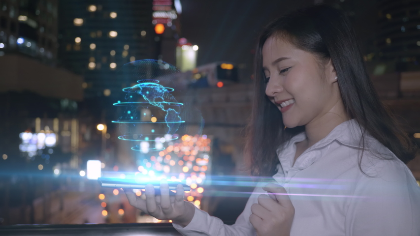 Young smiling business asian woman using smart phone interact a holograms big data 3D Earth, network advanced technology of the future on the smart phone screen. background city Bangkok Thailand. | Shutterstock HD Video #1041177211