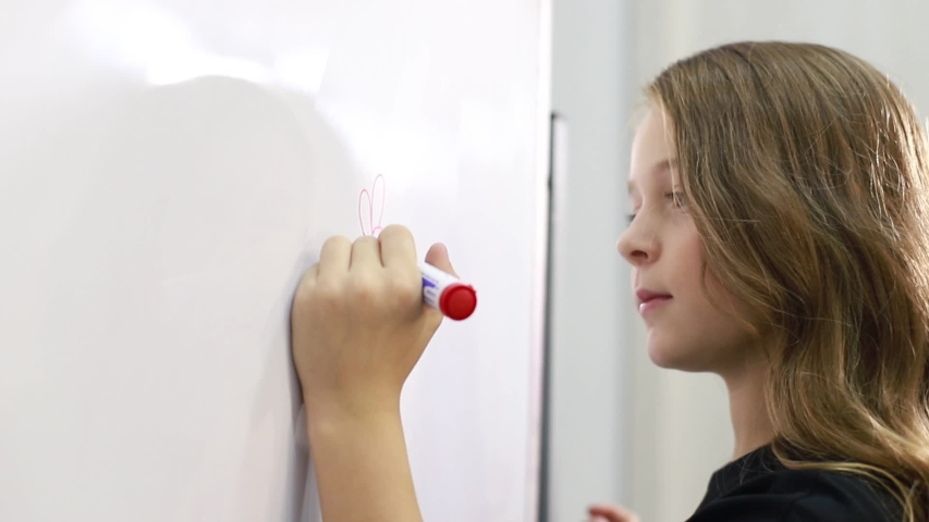 Little girl at school writes equation on the board, a smart young generation of children | Shutterstock HD Video #1041224461