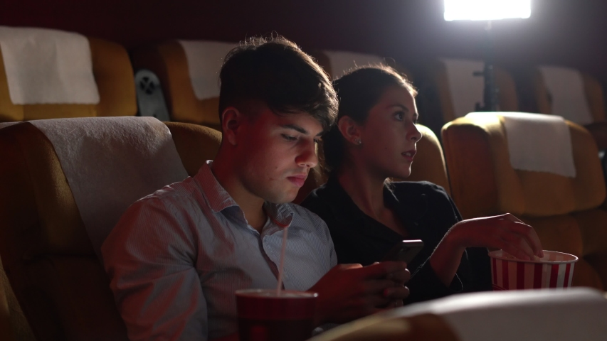 Men playing games on mobile phones he makes his girlfriend annoy and Interfere with watching the movie. | Shutterstock HD Video #1041306271