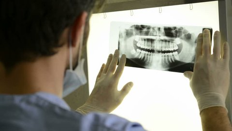 Closeup of dentist looking at dental x-ray plate. Dental x-ray plate leaning on the light table while the dentist examines the dental arch.