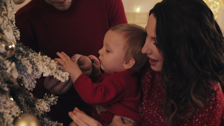 Cheerful Young Family with Baby Boy Decorating Christmas Tree at their Bright Cosy Living Room Looking Happy Smiling. Baby Holds Christmas Ornament Concept of Family Holidays and New Year Close Up | Shutterstock HD Video #1041460261