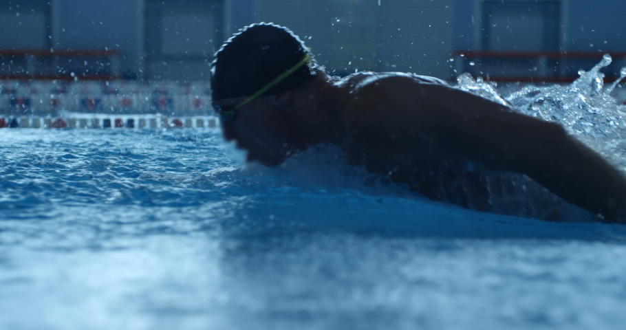 A professional swimmer raising a lot of splashes is swimming in butterfly style along his path in the pool. Slow mo, slo mo, slow motion, high speed camera | Shutterstock HD Video #1041554251