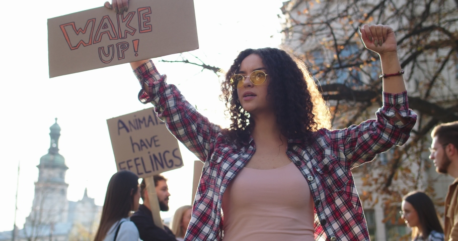 "Young Caucasian curly pretty girl in sunglasses holding a poster ""Wake up"" and fighting for rights of animals and nature activism at the protest outside. Portrait shot. 