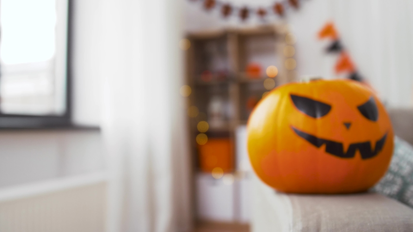 Holidays, decoration and party concept - jack-o-lantern pumpkin with scary smiley on sofa at home on halloween | Shutterstock HD Video #1041835081