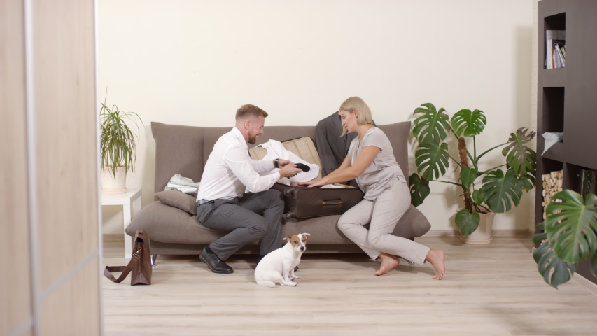 Tracking shot of cheerful blond woman sitting on couch and helping her husband pack suitcase for business trip | Shutterstock HD Video #1041895321