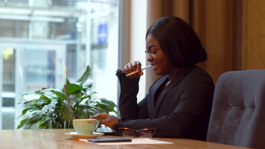 African american businesswoman working with laptop and papers. Busy woman paying bills online banking managing finances checking budget doing paperwork using computer sitting at desk   Shutterstock HD Video #1042268881