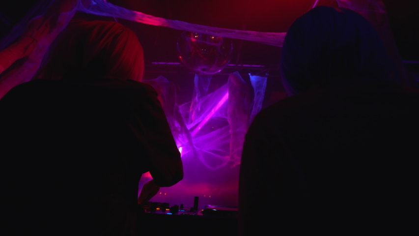 Two female djs performing at turntable in nightclub, Halloween celebration party   Shutterstock HD Video #1042282561