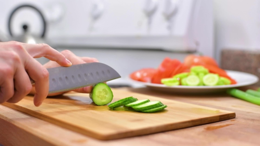 Female hands cut cucumber. Woman using kitchen knife is slicing fresh cucumber on wooden board | Shutterstock HD Video #1042455541