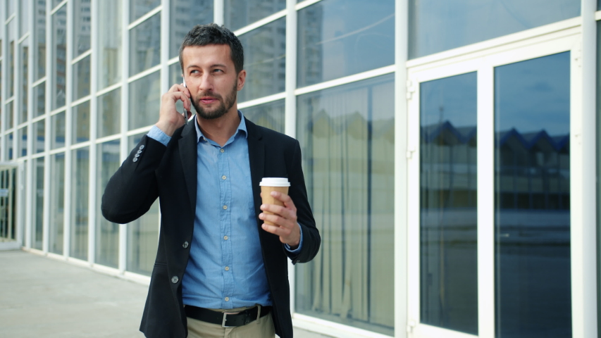 Cheerful entrepreneur handsome bearded guy is walking in city talking on mobile phone holding coffee discussing business news. Technology and communication concept. | Shutterstock HD Video #1042545331